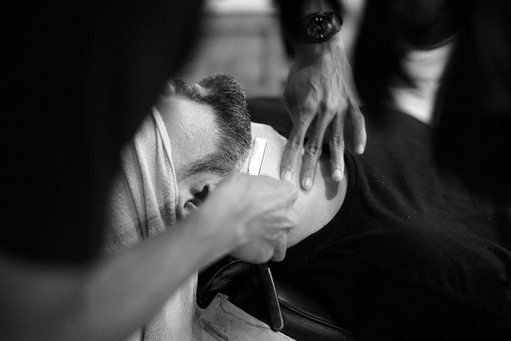 barber shaving man's beard