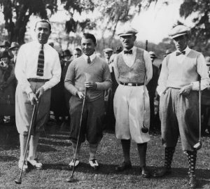 four men standing with golf clubs in 1930