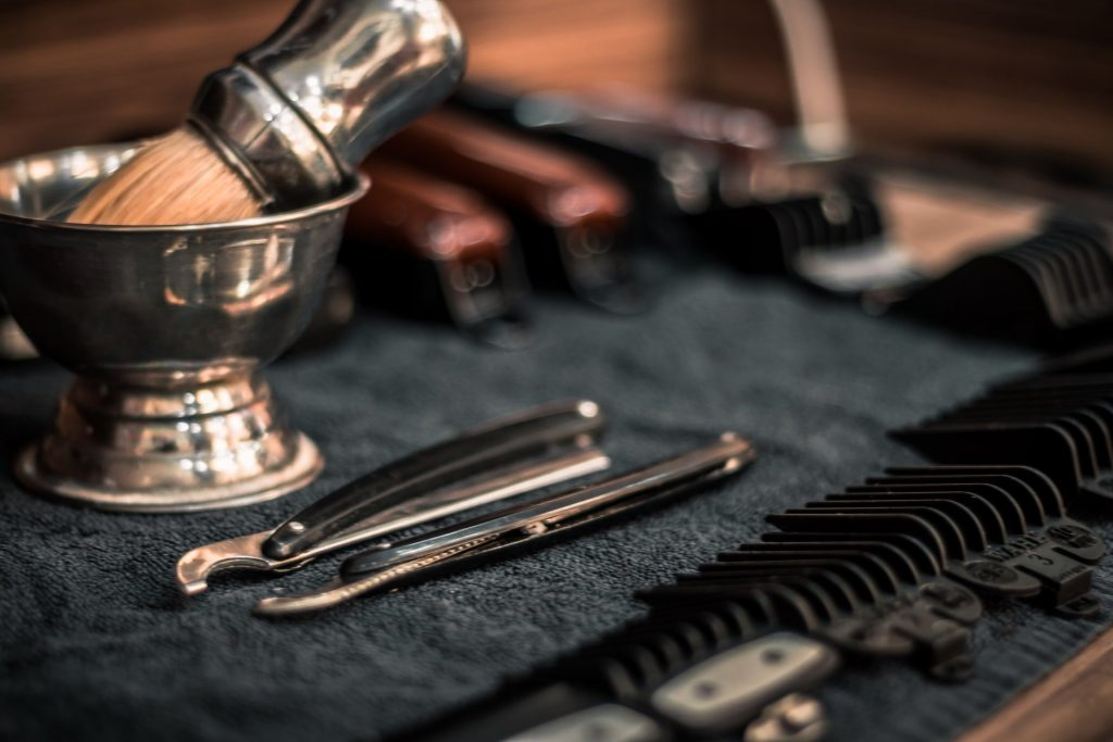 hair clippers, tweezers, and barber brush on table